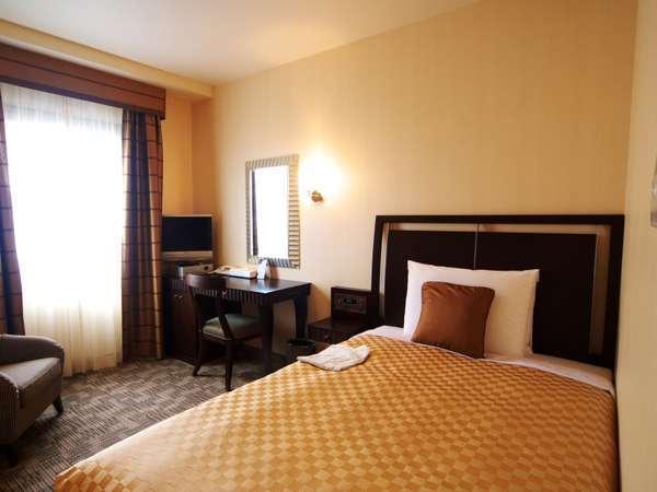 高級感があり、シックな客室。ベッドはシモンズ社製ポケットコイルベッド