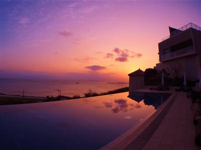 夕日に染まる海に溶け込むインフィニティープール