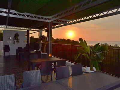 風が吹き抜ける開放的な屋上テラスレストランで夕日が沈む西海岸を一望