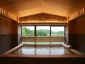 檜と軟石で設えた1階大浴場(男女入替制)