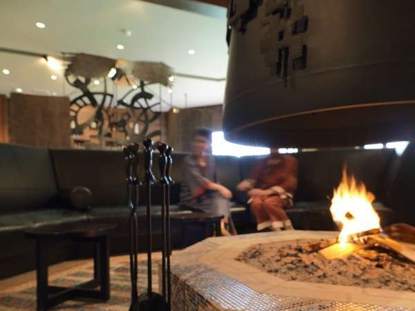 中央に暖炉を設けたメインラウンジ「回」でゆったりとチェックイン